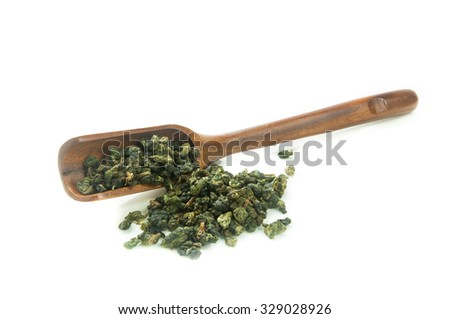 Green tea leaves and wooden scoop isolated on white background - stock photo