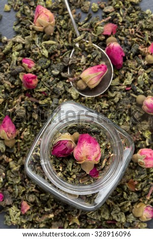 Green tea leaves with rose buds. Top view. - stock photo