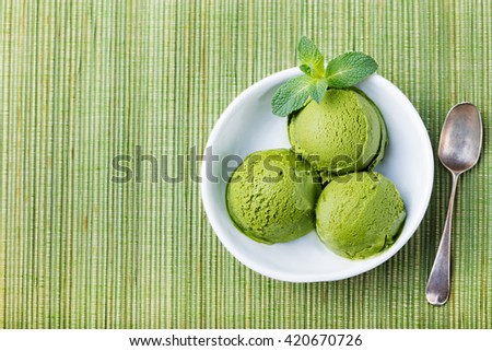 Green tea matcha ice cream scoop in white bowl on a wooden background ...