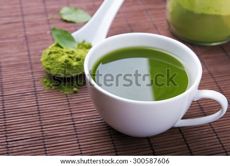 Green tea matcha in a white cup on the brown mat close-up - stock photo