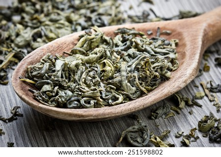 Green tea on wooden surface with spoon. - stock photo
