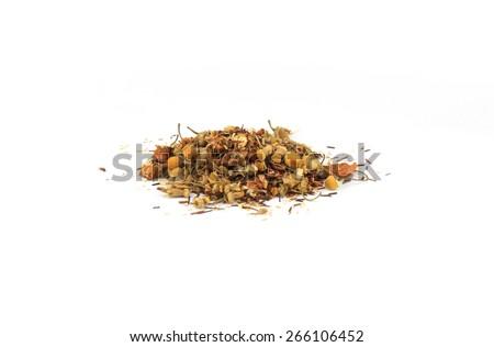 Green tea (rooibos, chamomile flowers, apple, cloves, cardamom, fennel, hops flowers) on white background. - stock photo