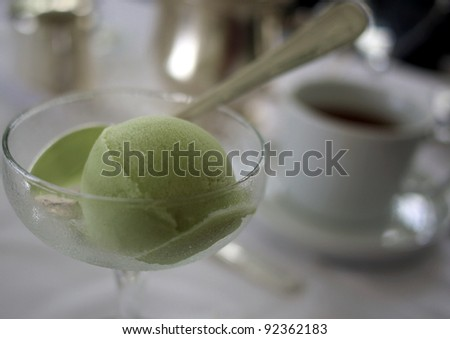 Green tea sorbet and tea in the background on a high tea table - stock photo