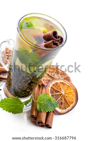 Green tea with cinnamon, mint, slices of lime and orange peel.. - stock photo