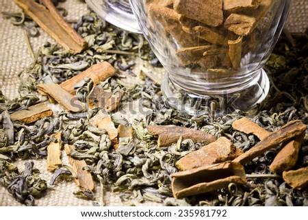 Green tea with cinnamon on linen fabric. - stock photo