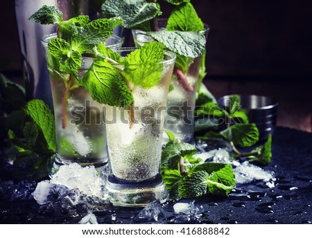 Green tea with ice, mint and white rum, dark background, selective focus - stock photo