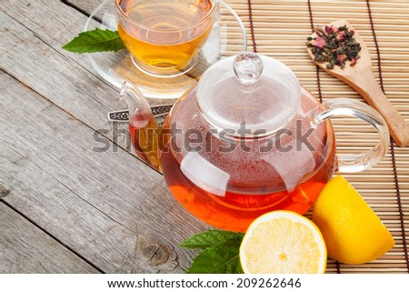 Green tea with lemon and mint on wooden table. Closeup with copy space