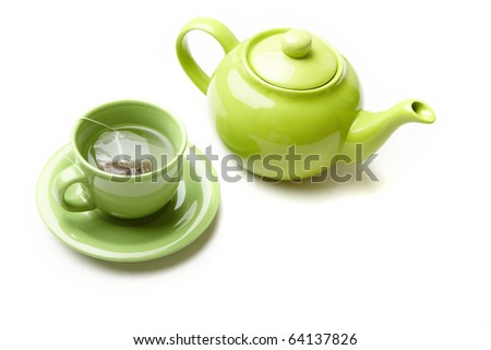Green teapot and teacup with tea bag on a white textured photo. Natural colors - stock photo