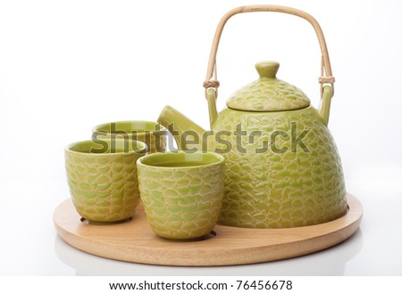 Green teapot with three cups on wooden tray - stock photo