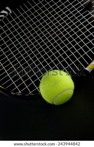 Green Tennis Ball and Black Racquet on Dark Background