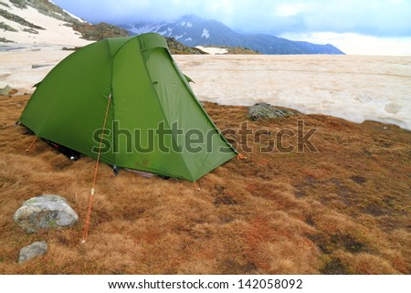 Green tent in bad weather on the mountain - stock photo