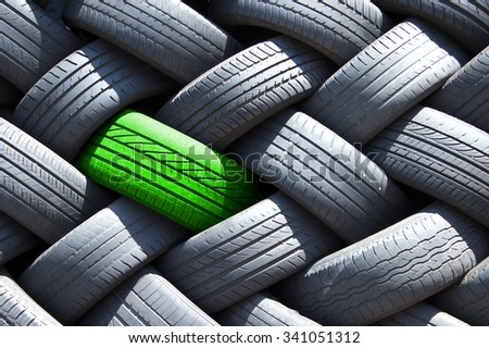 Green tire in a stack of tires - stock photo