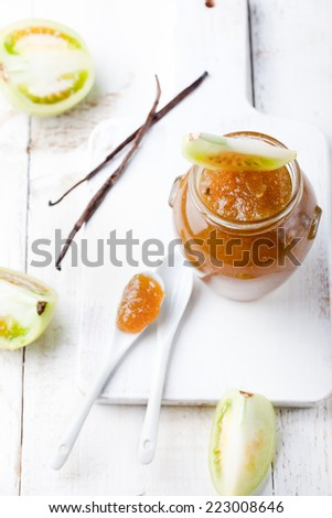 Green tomatoes jam with vanilla pods in a glass jar on a white wooden background. - stock photo