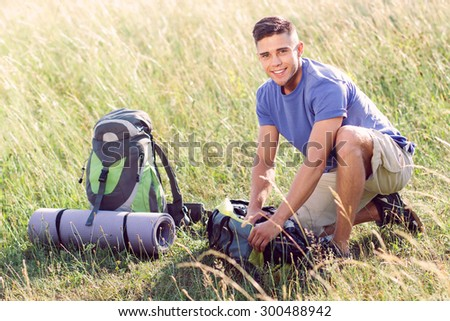 Green tourism.  Portrait of a young handsome tourist wearing blue t-short and beige shorts, sitting in the field fastening his bag smiling - stock photo