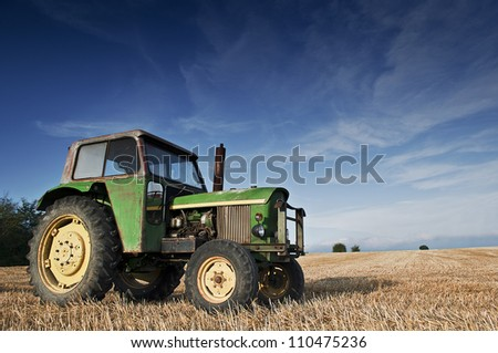 Green tractor in a harvested field - stock photo