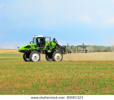 green tractor is spraying field - stock photo