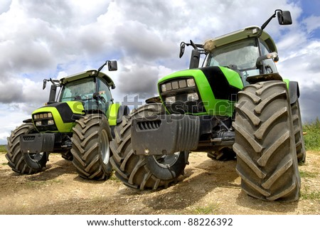 Green tractors in the field with a cloudy sky - stock photo