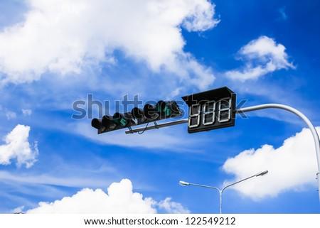 green traffic light against blue sky - stock photo