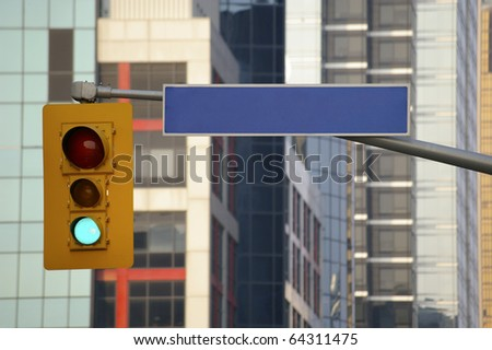 green traffic light and blank street sign with office building in background - stock photo