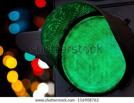 Green traffic light with colorful unfocused lights on a background - stock photo