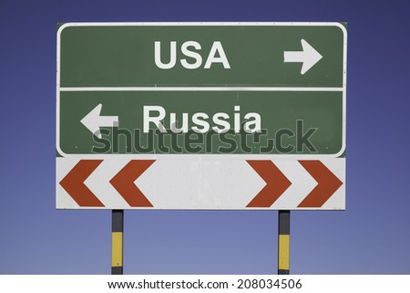 green traffic sign in front of a blue sky, horizontal arrows showing two directions and a red white road warning post. Business concept for the relations or conflicts between two Nations: USA, Russia - stock photo