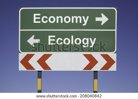 green traffic sign in front of a blue sky, horizontal arrows showing two directions and a red white road warning post. Business concept for decision: Choose between ecology and economy - stock photo