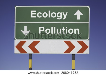 green traffic sign in front of a blue sky, horizontal arrows showing two directions and a red white road warning post. Ecological concept for decision: Choose btween ecology abd pollution - stock photo