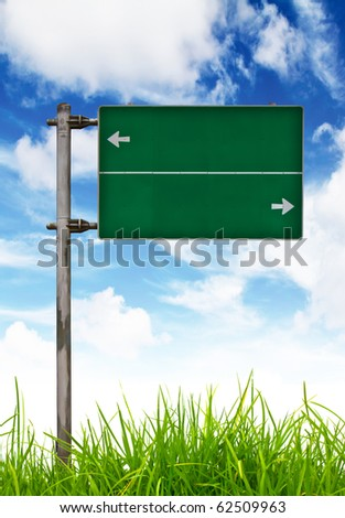 Green Traffic sign on green grass and blue sky. - stock photo