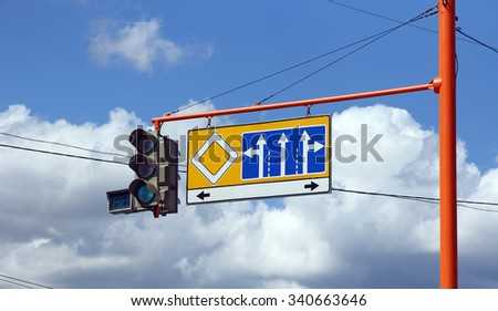 Green traffic signs with the direction of travel on a background of blue sky. - stock photo