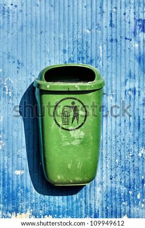Green trash basket on blue background - stock photo