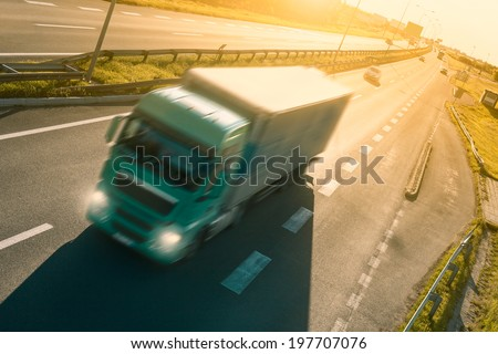 Green truck in motion blur on the highway at sunset - stock photo