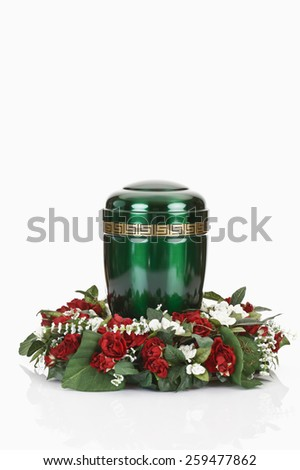 Green urn and floral wreath on white background - stock photo