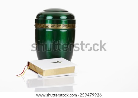 Green urn and white bible on white background - stock photo