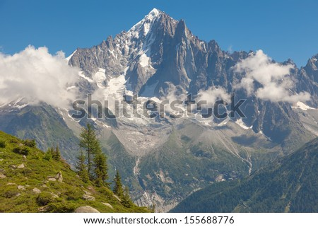 green valley surrounded by snow mountain - stock photo