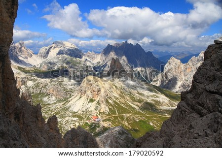 Green valleys and eroded mountains in the background, Dolomite Alps, Italy - stock photo