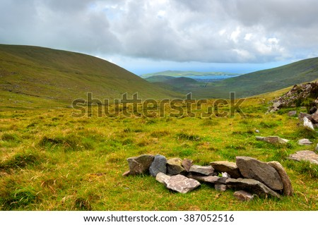 Green valleys with hills and lakes with moody sky over Ring of Kerry in County Kerry, Ireland - stock photo