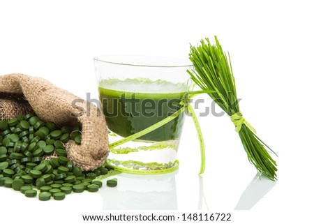 Green vegetable juice, green pills in brown natural sack and wheatgrass blades isolated on white background. Natural herbal alternative medicine. Healthy living.  Natural Superfood. - stock photo