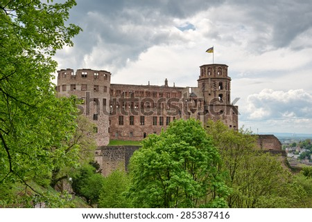 Green vegetation in front of the ruins of Heidelberg Castle, historical tourist attraction, under a dramatic cloudy sky, in Germany - stock photo