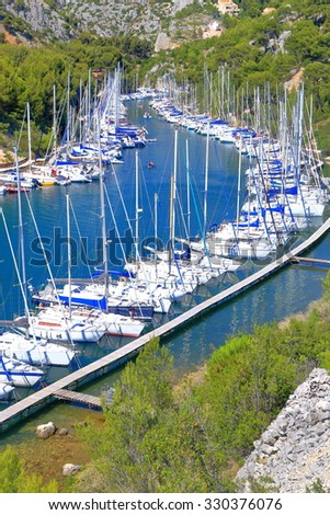 Green vegetation surrounds narrow canal with sea water called calanque and sail boats at anchor, Cassis, France