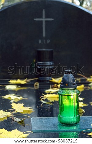 Green votive candle lit on black marble tombstone with engraved RIP sign - stock photo