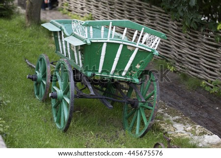 Green wagon horse. It located on a green grass by wattle fence. - stock photo