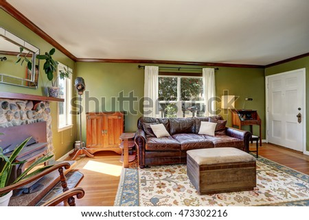 Green walls living room with stone fireplace and leather couch. Northwest, USA