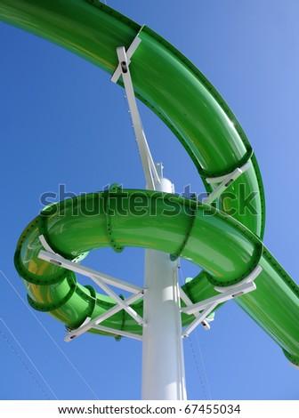 Green water slide at aquatic amusement park - stock photo