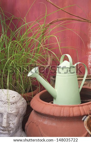 Green watering can in the garden