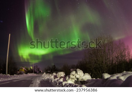 Green wavy northern lights over the winter road, Kola peninsula, Northern Russia - stock photo