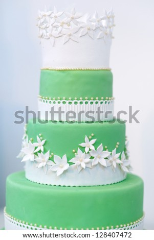 Green wedding cake decorated with sugar white flowers - stock photo