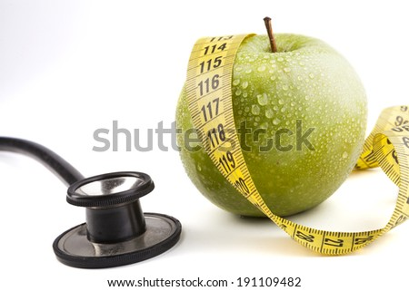 Green wet apple with yellow measuring tape and black stethoscope isolated on white background
