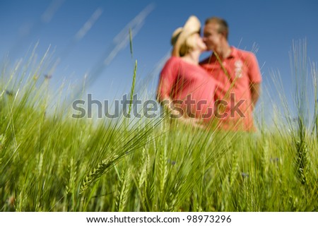 Green wheat field in the foreground and pregnant couple kissing in the background out of focus.