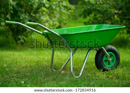 Green wheelbarrow in green garden, green background. New.