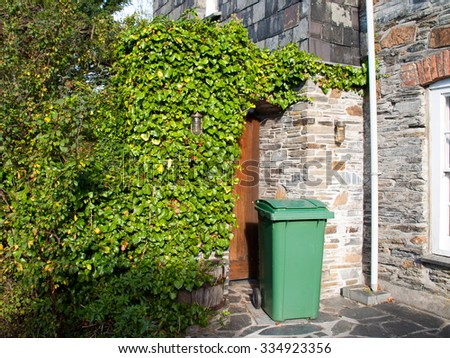 Green wheelie bin in front of a house entrance somewhere in Port Isaac in north Cornwall - stock photo